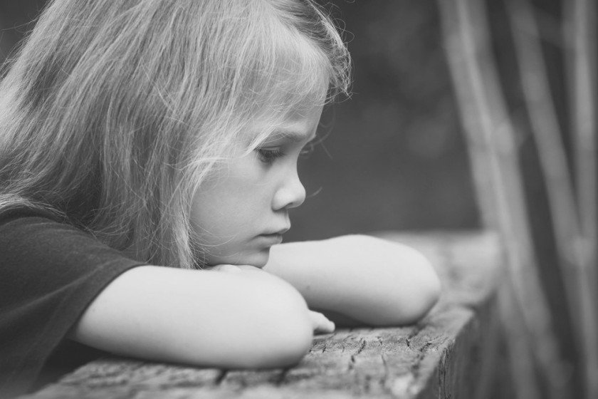Portrait of sad blond little girl sitting on the bridge at the day time